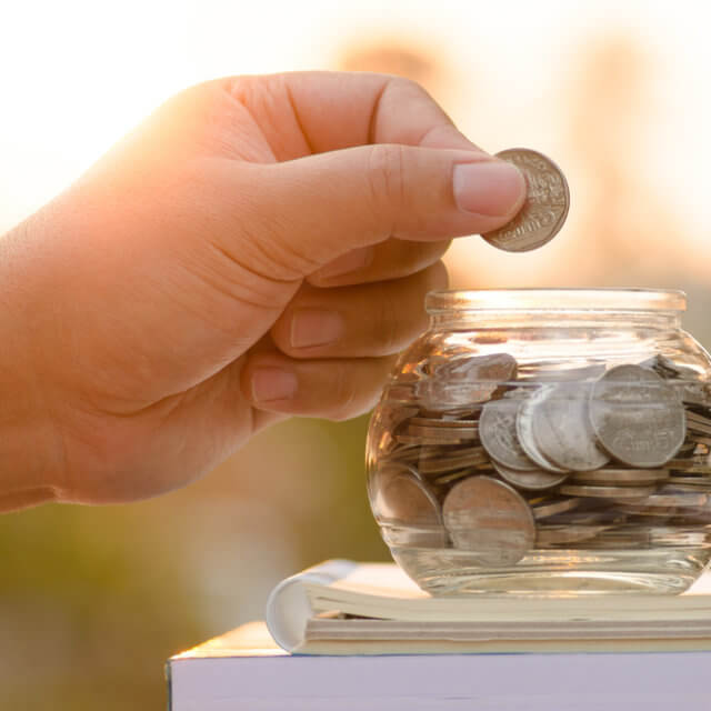 hand putting coins in jar atop a book to save for college