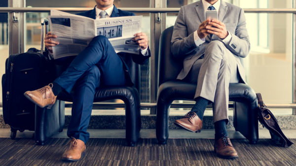 men sitting down reading the newspaper and on the phone