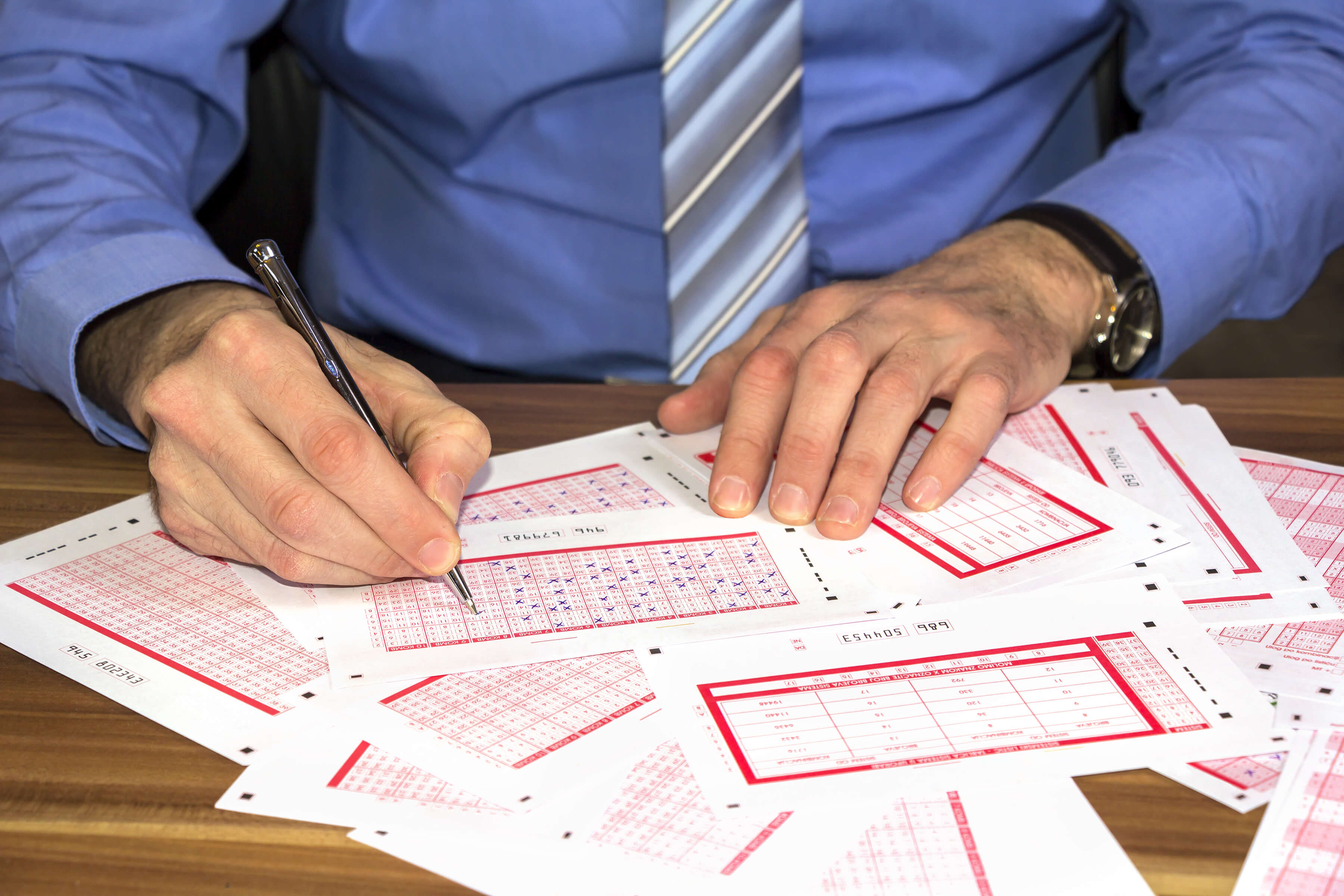Young businessman Marking on lottery ticket with a pen