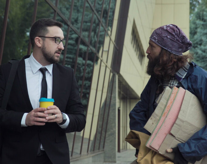 Wealthy businessman and homeless person look at each other, showing that the divide between the rich and the poor has never been wider due to the lack of affordable housing.