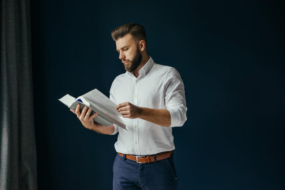 A man in white shirt reads a blue book