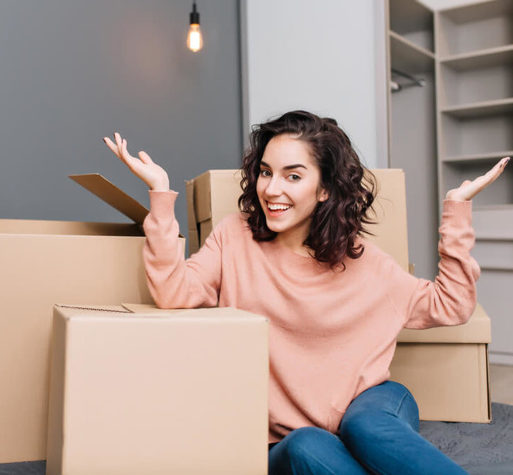Girl in pink sweater in front of boxes moving into her new apartment.