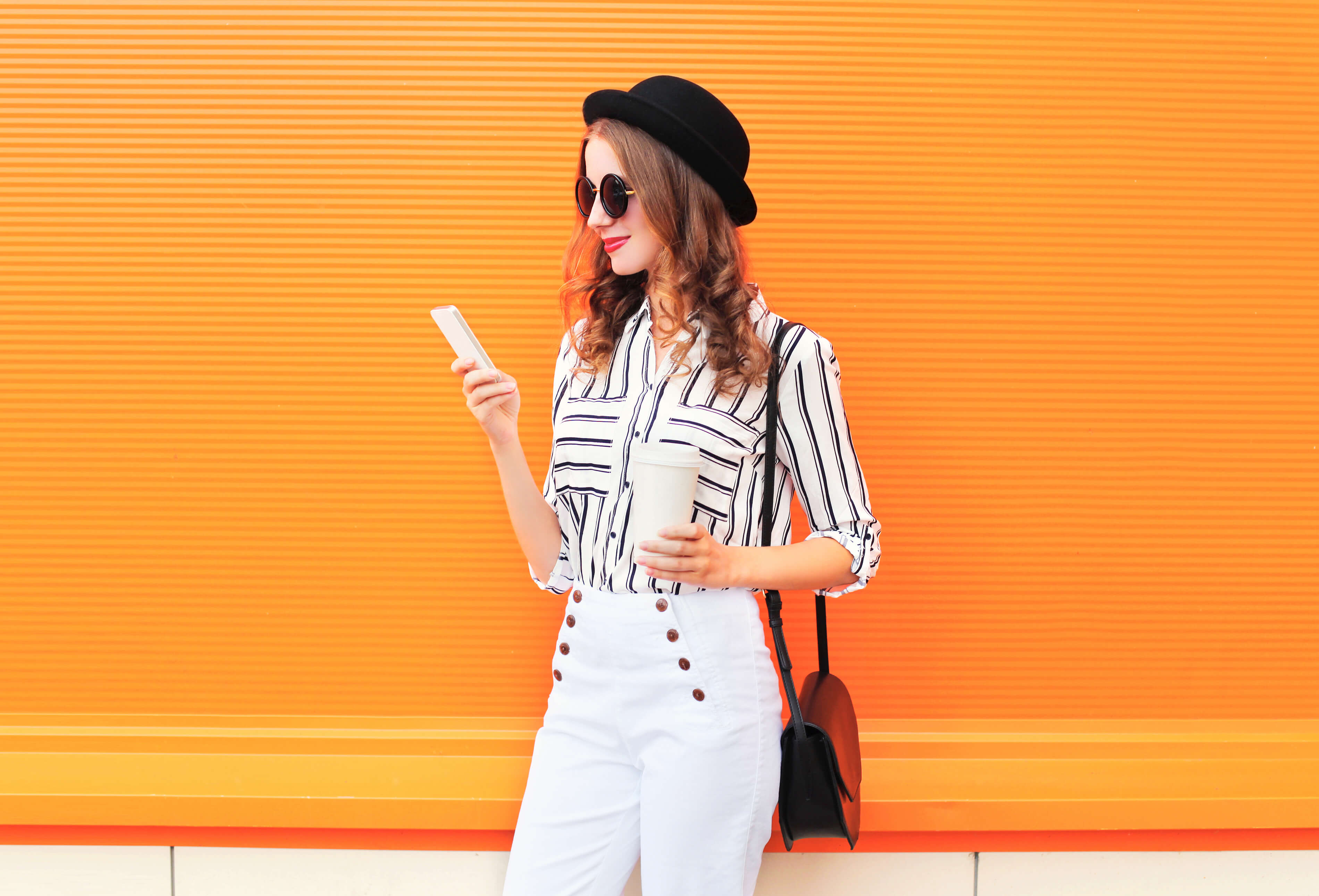 Woman in striped shirt looks at her smartphone in front of a bright orange background. Manage your personal branding better with Activate Worldwide.