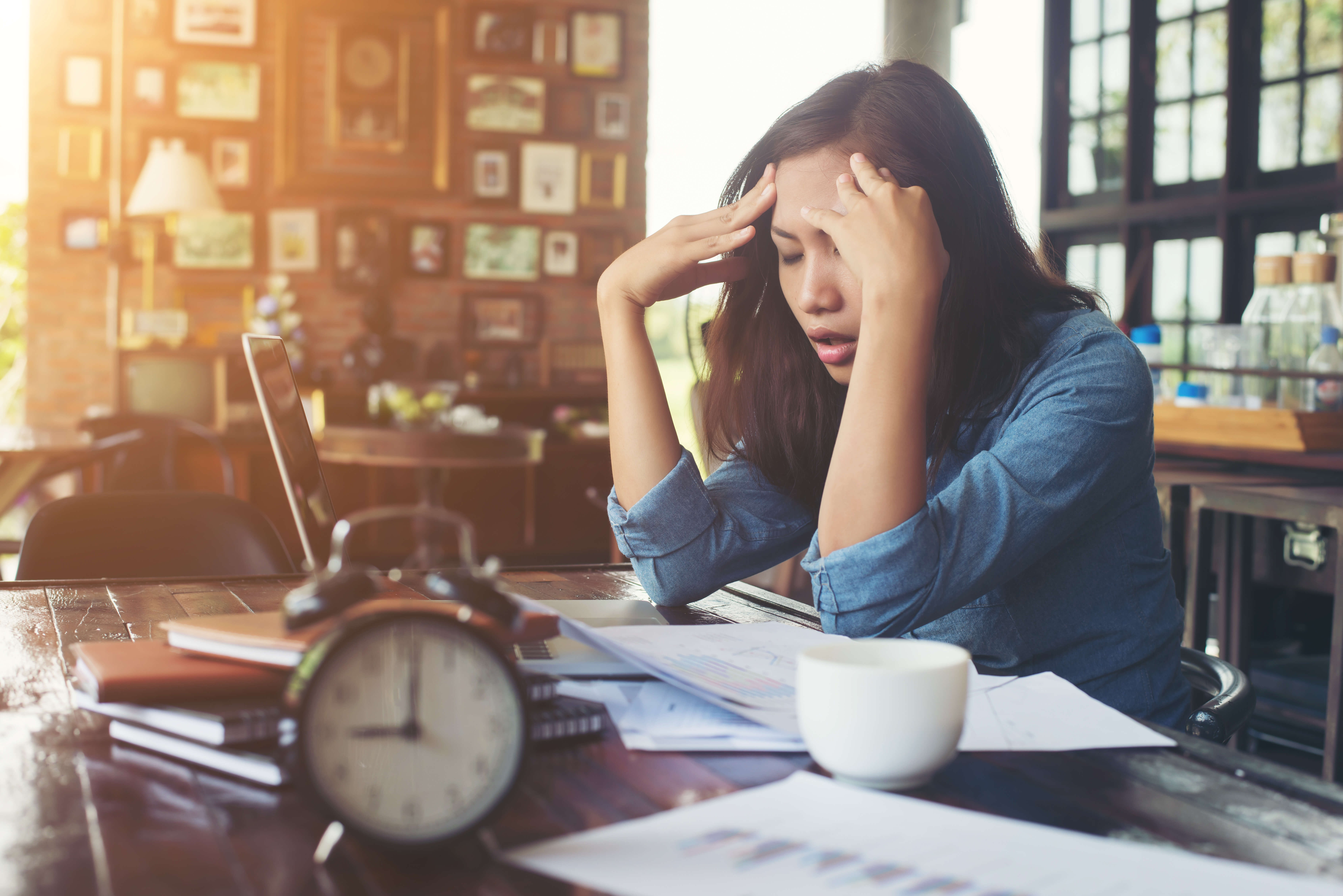 Exasperated woman pays bills at her desk. Don't let your credit score overwhelm you, rebuild your credit with Blackwood Credit.