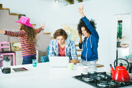 Women dancing around man in kitchen