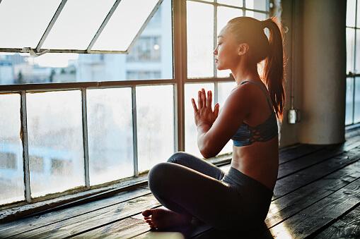 Woman meditating doing Yoga in Natural Light Studio