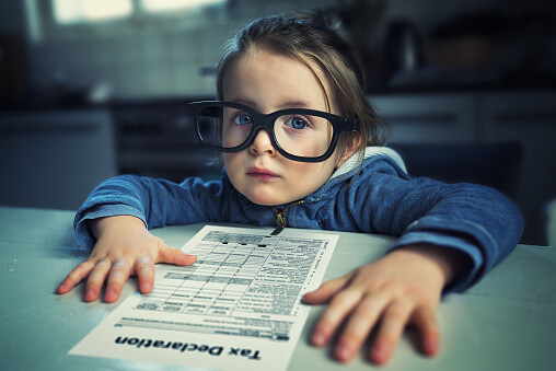 child in oversized glasses looking over tax forms