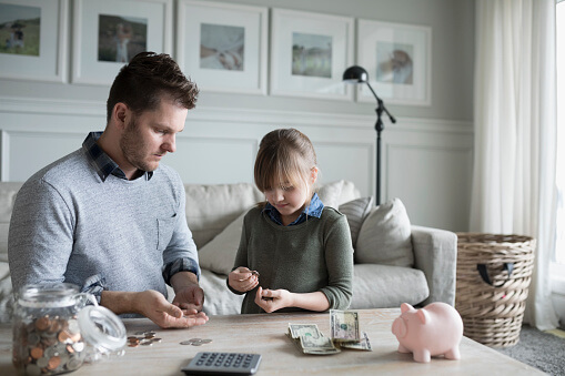 Father teaching daughter counting allowance money in living room