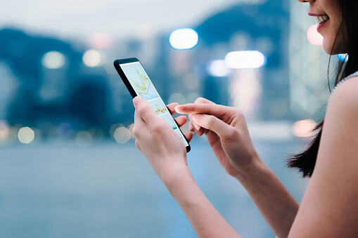 Woman checking financial trading data with smartphone in city