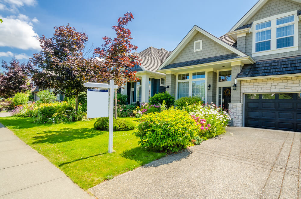 photo of modest suburban house with for sale sign in front yard