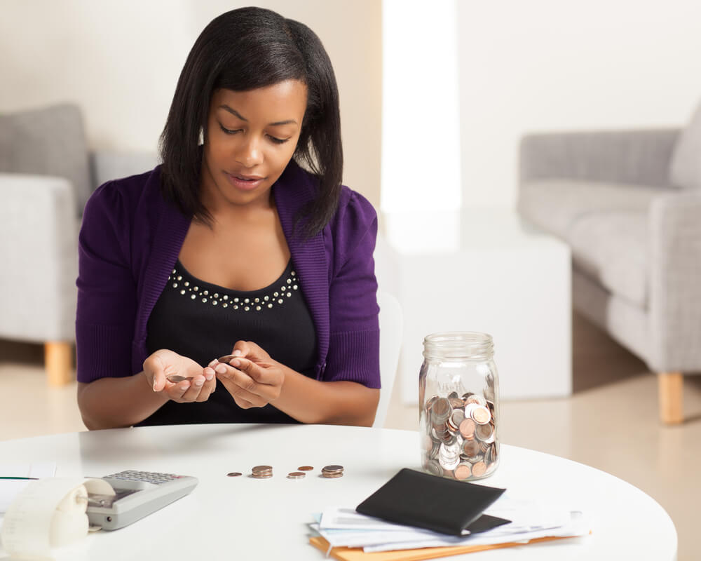young African American woman working on finances at home wearing purple jacket sitting at dining table.
