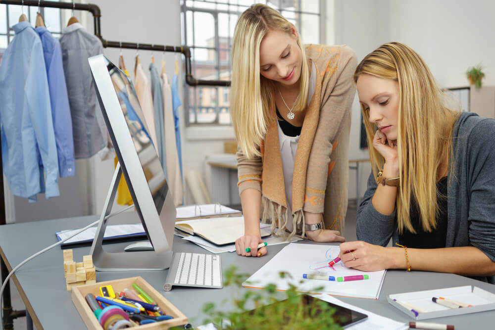 Two Fashion Stylist Women Sketching a New Design on a White Paper at the Table Inside the Office.