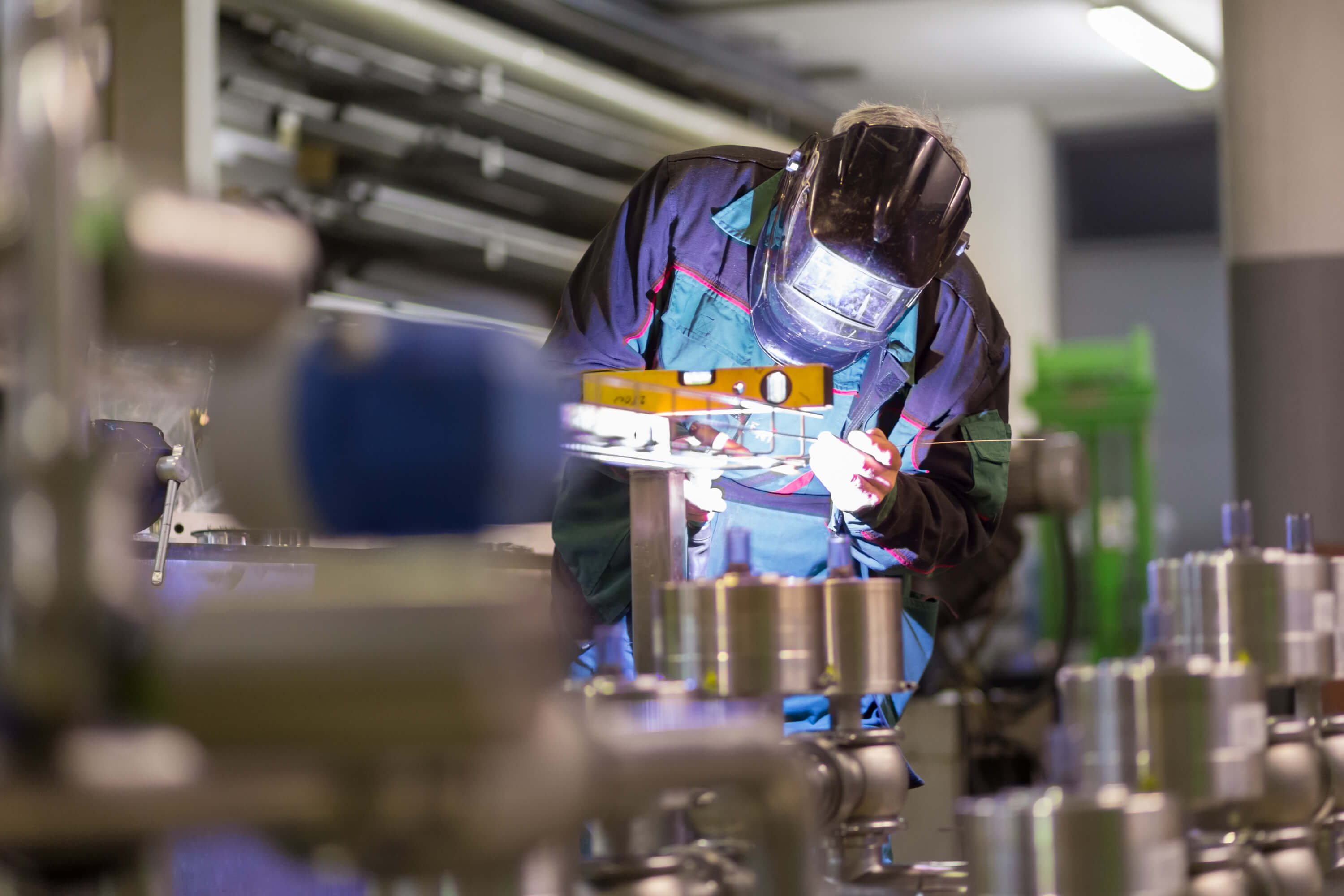 a worker wearing blue is welding materials in a factory