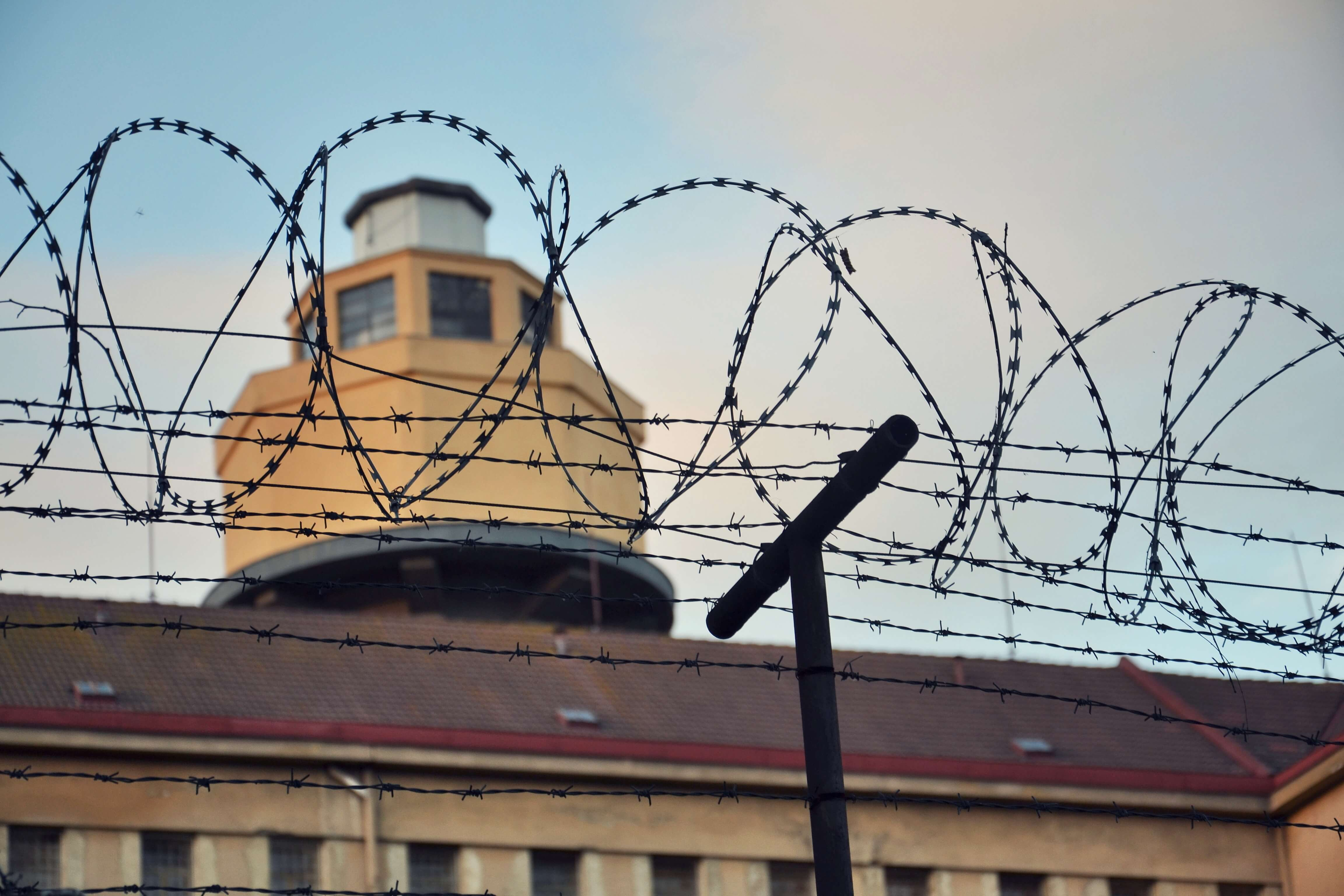 image of barbed wire fence in front of prison building