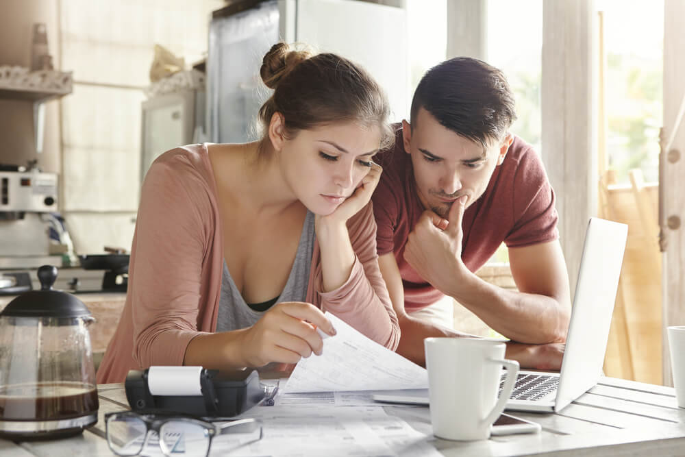 Worried young Caucasian married couple reading important notification from bank while managing domestic finances and calculating their expenses at kitchen table, using laptop computer and calculator