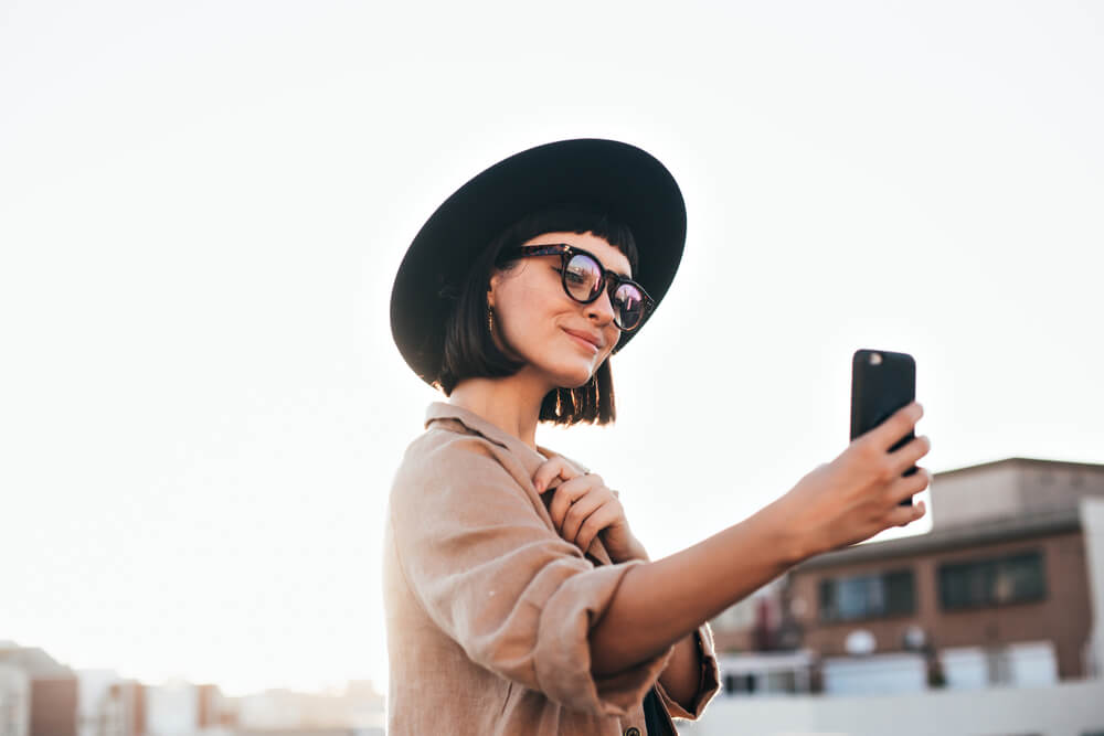 fashion trendy and hipster millennial woman or girl makes selfie on smartphone camera to share on internet social media channels, self absorbed new generation of young people