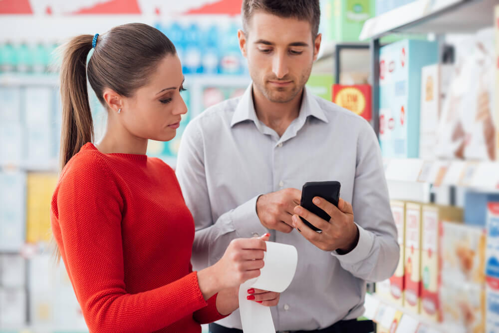 Couple doing grocery shopping at the supermarket they are checking a long receipt and using apps on the phone