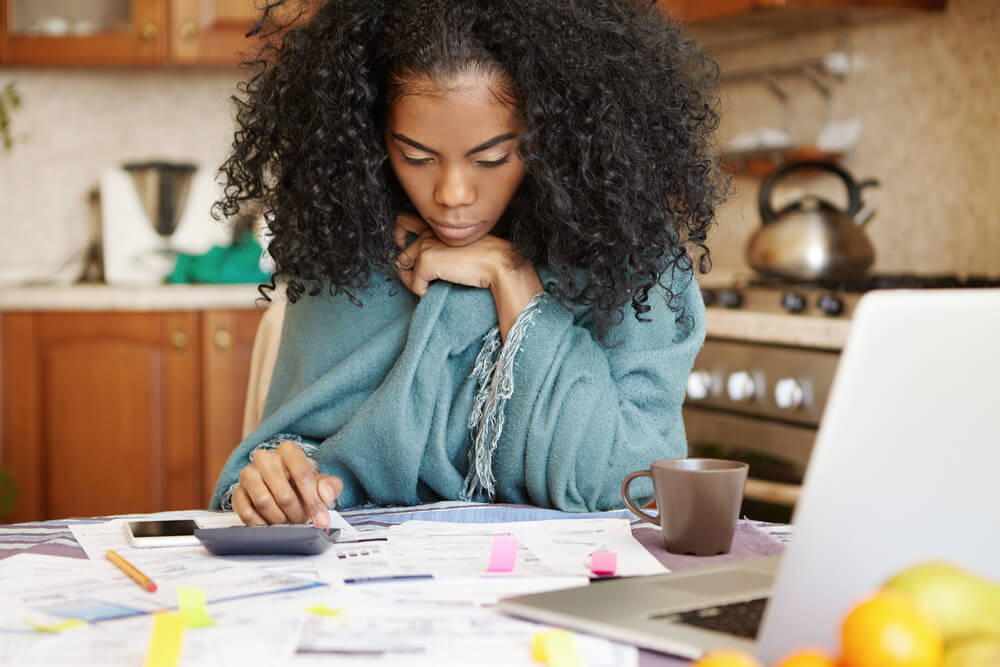 African-American woman with many debts feeling stressed calculating finances, siting at kitchen table with papers, laptop, making calculations on calculator, trying to make ends meet